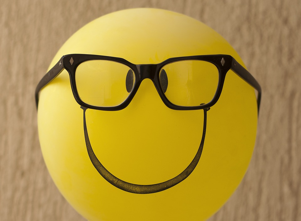 Emoticono de color amarillo con gafas