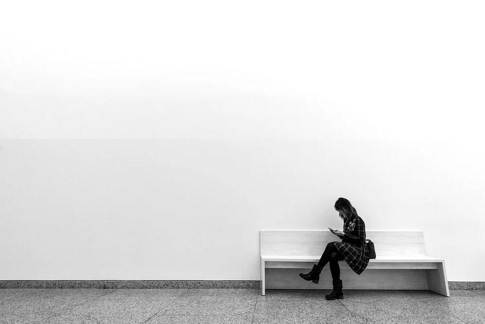 Fotografía en blanco y negro de mujer sentada en un banco mirando el móvil
