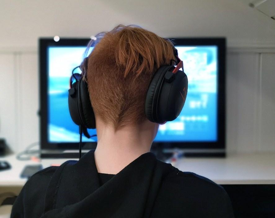 Niño de espaldas y con cascos en las orejas jugando a videojuego