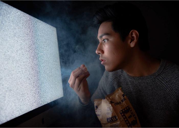 chico con bolsa de palomitas disfrutando de la tele
